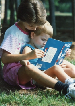 Erin, about 7 years old, trying to read to her  younger brother